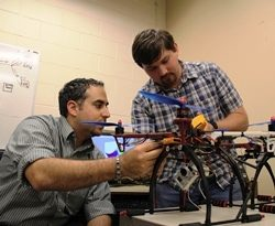 Faculty working with a student on a drone