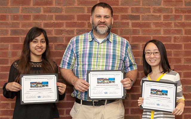 Dr. Jeffrey P. Kaleta, Jingjing Yin and Ms. Sushmita Khan receiving an award